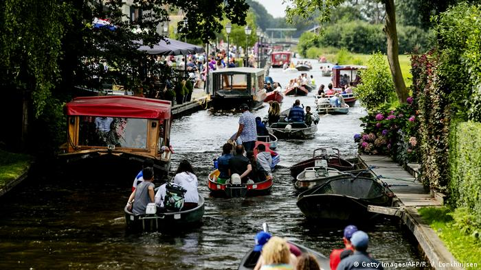 People take a boat ride on a river in Giethoorn, a well-known destination for tourists and day-trippers, in the Netherlands
