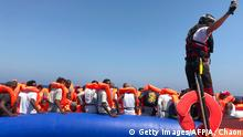A crew member of the 'Ocean Viking' rescue ship, operated by French NGOs SOS Mediterranee and Medecins sans Frontieres (MSF), stands ready on board of a rhib, an inflatable dinghy, as they approach an inflatable boat carrying some 81 migrants, during a rescue operation in the Mediterranean Sea on August 11, 2019. - The rescue operation comes as a dispute escalates over which countries will take in migrants rescued by different charity ship operating in the area, as mild Mediterranean weather increases the number of people trying to make their way to Europe from Africa. (Photo by Anne CHAON / AFP) (Photo credit should read ANNE CHAON/AFP/Getty Images)