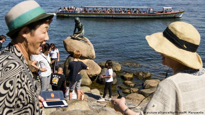 Tourists gather near the statue of The Little Mermaid in Copenhagen, Denmark