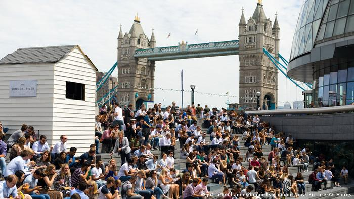 Crowds of tourists and office workers gather near Tower Bridge in London, England