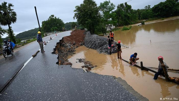 Workers repair a portion of a damaged road