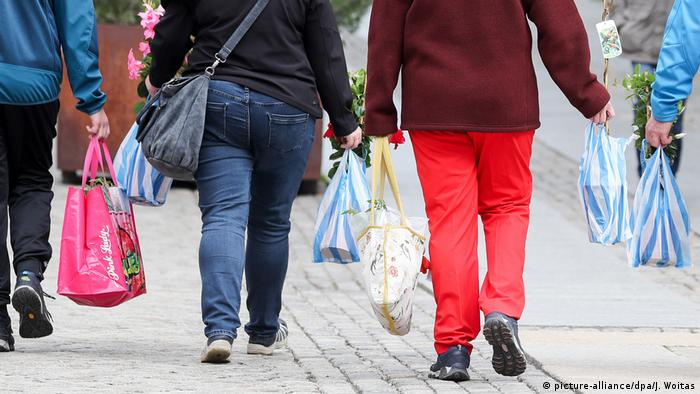 Germans holding plastic bags (picture-alliance/dpa/J. Woitas)