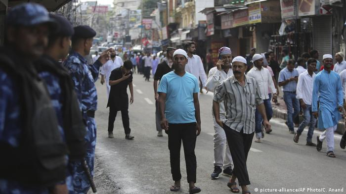 People walk past Indian security forces after prayers in Jammu, India