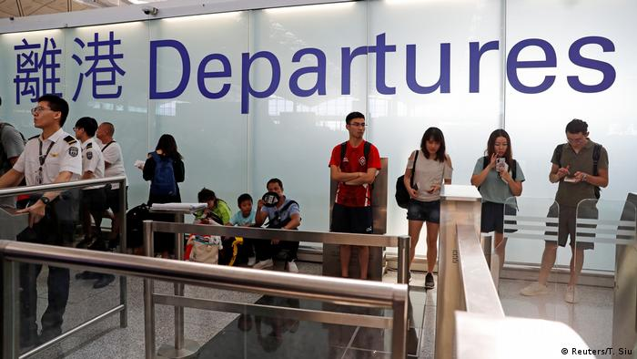 People standing under a Departures sign at Hong Kong International Airport during a protest in 2019 (Reuters/T. Siu)