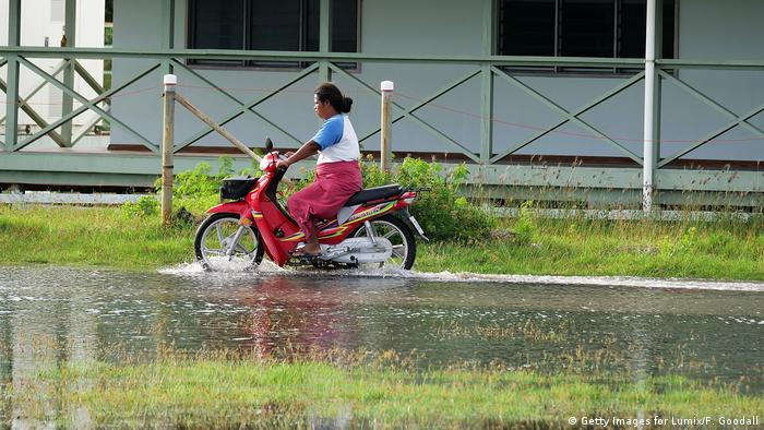 A woman drives a motorcycle through a flooded street