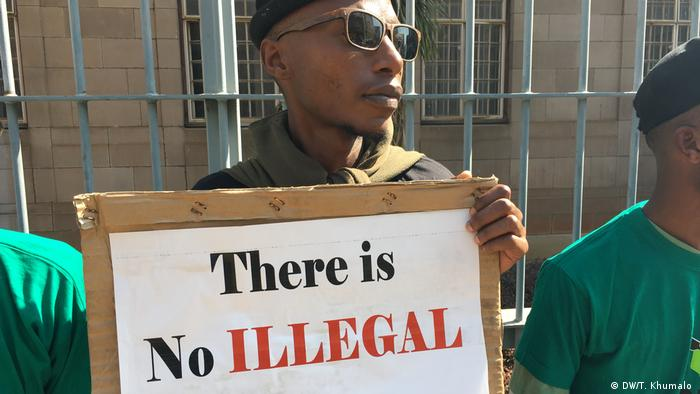 a demonstrator holding up a sign saying There is no illegal