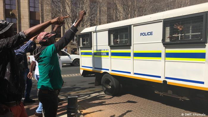 Demonstrators raise their arms in support in front of a bus containing the arrested migrants (DW/T. Khumalo )