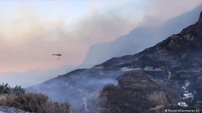 A helicopter flying over smoke-covered mountains