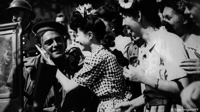 Young Parisian women greet Allied soldiers as they enter Paris during its liberation in late August 1944