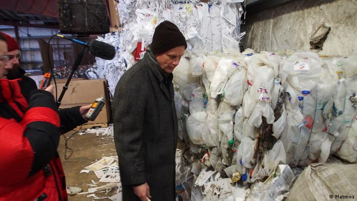 Three men stand in front of plastic waste stacked in a recycling center. One is holding a microphone