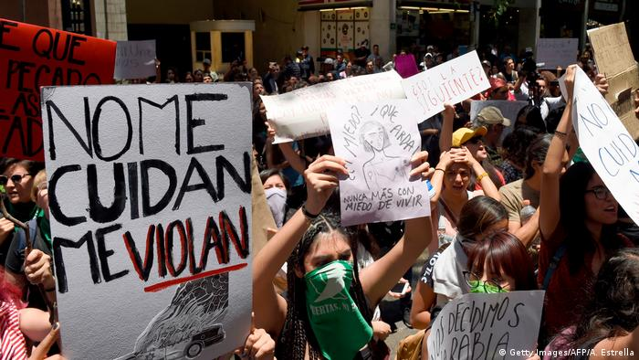 People in Mexico City holding up signs and protesting a lack of state action against violence against women