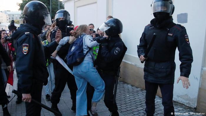 Russian protester Daria Sosnovskaya struggles with law enforcers