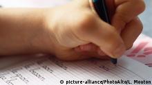 Hand holding ballpoint pen on notebook, close-up | Verwendung weltweit, Keine Weitergabe an Wiederverkäufer.