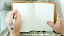 A left-handed person writes in a book (picture-alliance/PhotoAlto/O. Dimier)