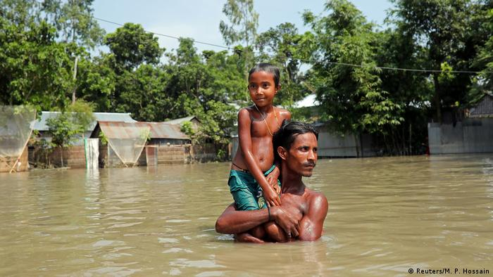 A man carries a child in floodwater