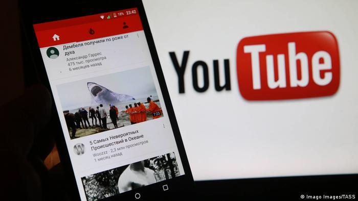 Smartphone na kojem se mogu vidjeti sadržaji stranice YouTube-a na ruskom
