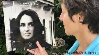 Susanne Spröer hält ein Plattencover von Joan Baez in der Hand. Darauf ein Porträtfoto von Baez und der Titel Where are you now, my son?