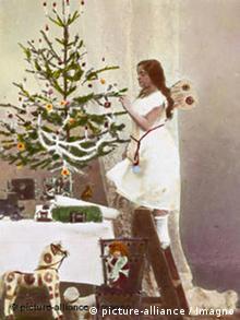Als ein Engel verkleidetes Mädchen schmückt einen Weihnachtsbaum (Foto: dpa)