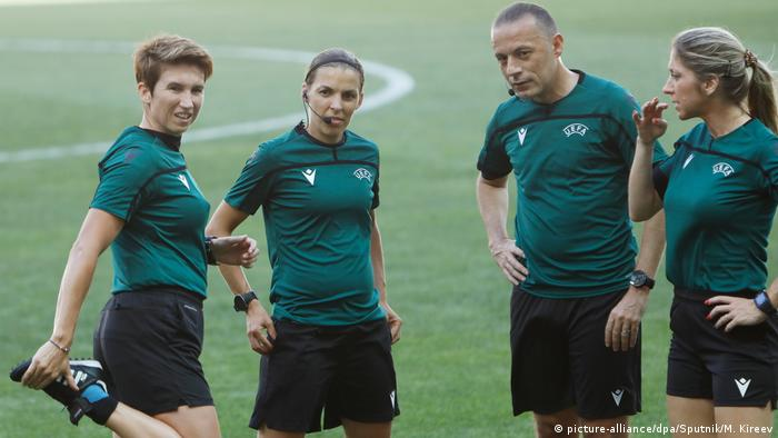 The main referee Stephanie Frappart, second left, assistant referees Michelle O'Neill, left, and Manuela Nicolosi, right, and fourth official Cuneyt Cakir warm up during a training session ahead of the Super Cup match between Liverpool and Chelsea, in Istanbul, Turkey. (picture-alliance/dpa/Sputnik/M. Kireev)