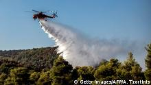 A firefighting helicopter drops water over a fire near the village of Makrimalli on the island of Evia, northeast of Athens, on August 14, 2019. - - Hundreds of villagers were evacuated on August 13 and the Greek prime minister cancelled a vacation as scores of firefighters battled a major wildfire on the country's second-largest island of Evia, authorities said. (Photo by ANGELOS TZORTZINIS / AFP) (Photo credit should read ANGELOS TZORTZINIS/AFP/Getty Images)