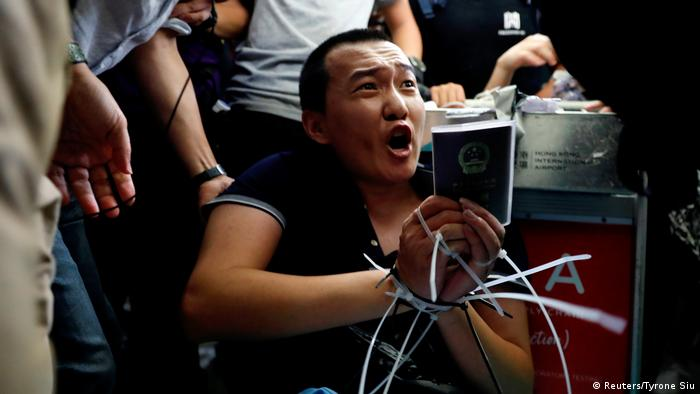 A reporter from the Global Times restrained in plastic zip ties in the Hong Kong airport