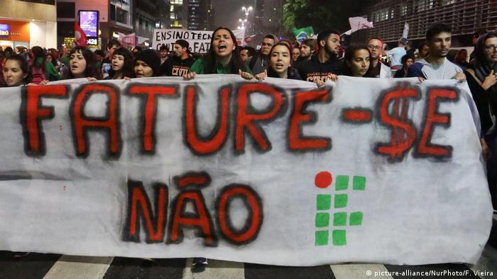 Manifestantes marcham na rua atrás de faixa Fature-se não, com letras vermelhas