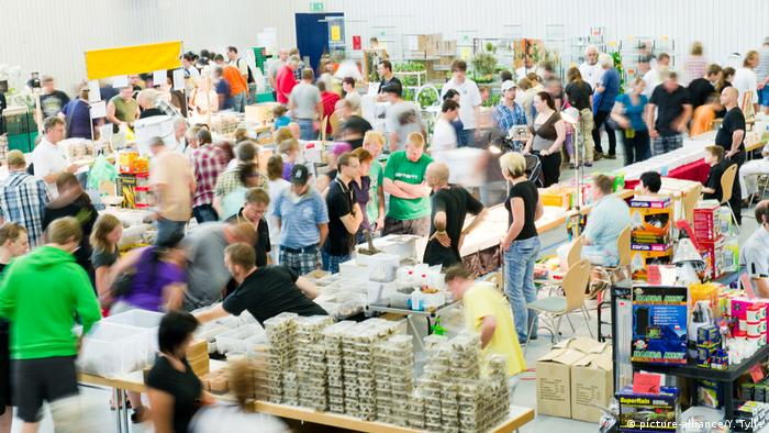People in a hall at a trade fair. Boxes are stacked around them