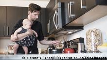 Father holding baby daughter (2-5 months) while stirring food, Vater haelt Tochter (2-5 Monate), waehrend Essen Ruehren | Verwendung weltweit, Keine Weitergabe an Wiederverkäufer.