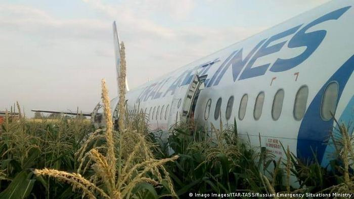 A Ural Airlines plane sits in a cornfield