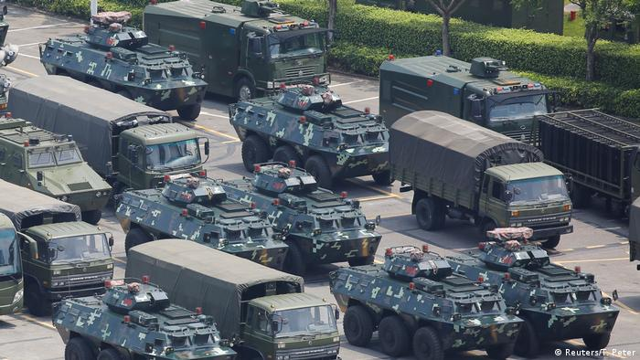 Military vehicles are parked on the grounds of the Shenzhen Bay Sports Center in Shenzhen, China
