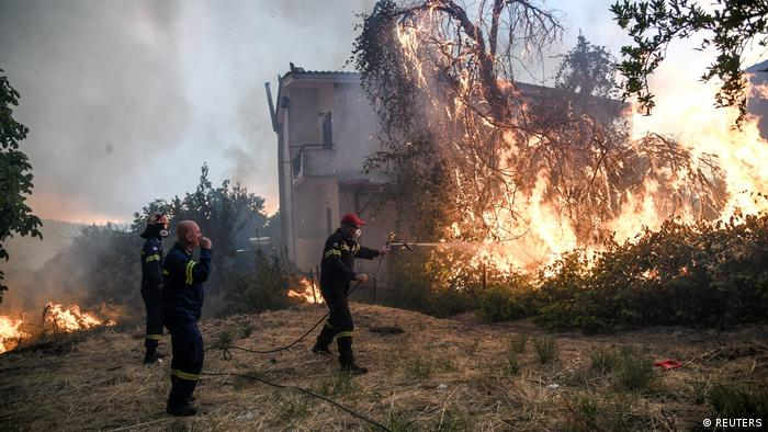 Firefighters try to extinguish a fire burning near a house as a wildfire burns in Greece (REUTERS)