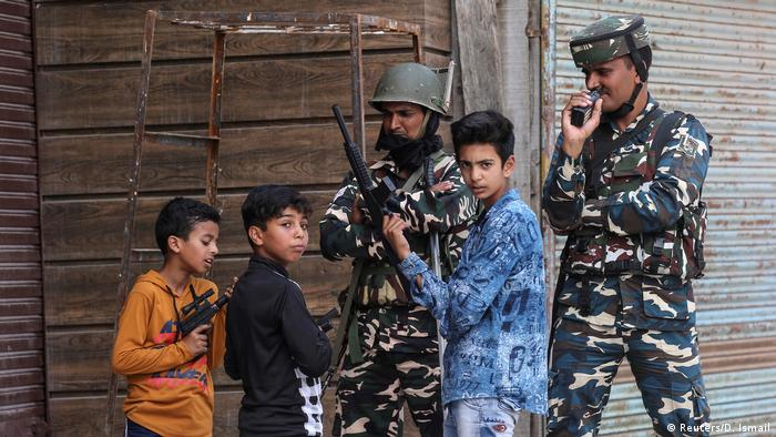 Children play with toy guns next to Indian security force personnel during restrictions after the scrapping of the special constitutional status for Kashmir by the government, in Srinagar, August 13, 2019