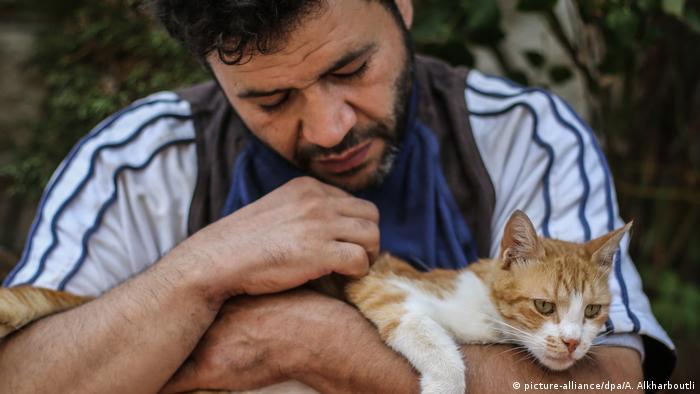 Alaa sostiene a un gato entre sus brazos.