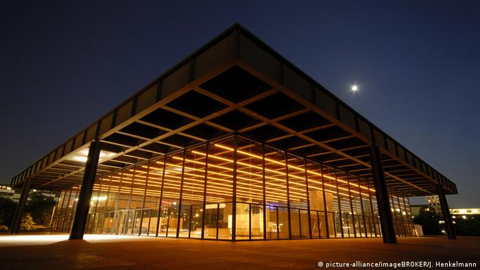 A large modernist structure with glass walls at night