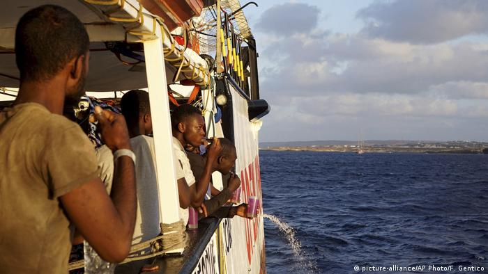 Migrants stand on board the rescue ship Open Arms as they approach Italy's Lampedusa island