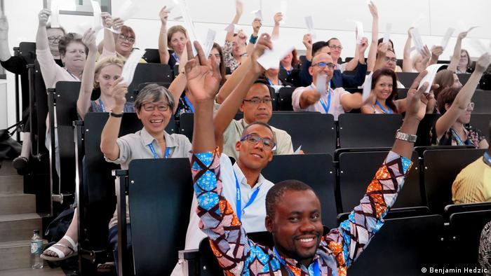 Tagungsteilnehmer beim IDV halten Stimmzettel hoch