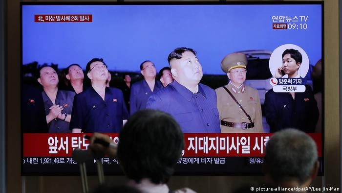 South Koreans follow a newscast showing footage of North Korean leader Kim Jong Un watching missiles being launched