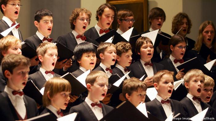 Choirboys with black jackets and red bowties holding up their scores and singing (Imago Images/S. Schellhorn)