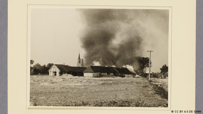 Foto antiga de grande propriedade no campo com fumaça ao fundo