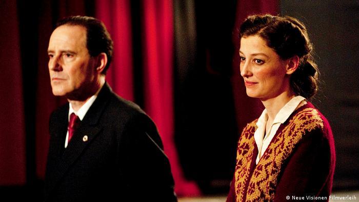 Filmstill Und der Zukunft zugewandt Szene mit Mann und Frau vor rotem Vorhang