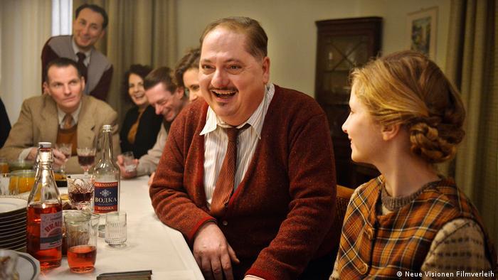 Filmstill Und der Zukunft zugewandt Szene mit verschiedenen Leuten an gedecktem Tisch