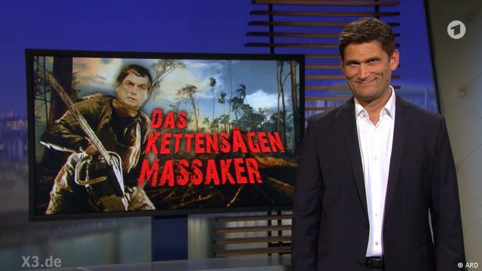 O massacre da serra elétrica diz, em alemão, fotomontagem com Bolsonaro, atrás de apresentador