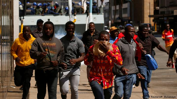 Zimbabwean protesters run from tear gas (Reuters/P. Bulawayo)