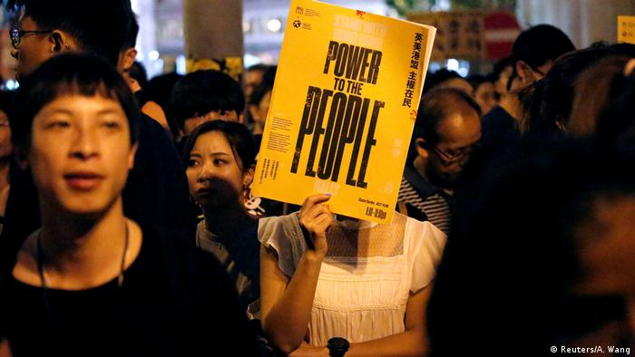 Woman holds up Power to the People placard in Hong Kong