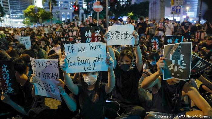 Protesters in Hong Kong hold up signs in the city's Chater Garden (picture-alliance/AP Photo/K. Cheung)