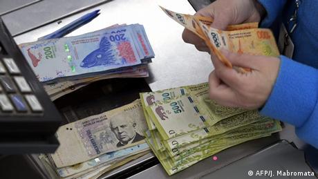 A cashier counts Argentine peso bills