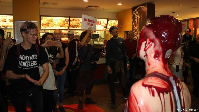 Blood-smeared woman and other protesters in McDonald's (DW/C. Winter)