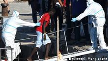 An unaccompanied minor from the Open Arms migrant rescue ship disembarks from the vessel