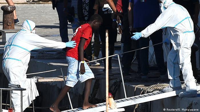 Jovem é retirado de navio com ajuda de duas pessoas trajando roupas de proteção