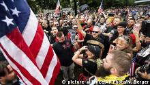 Members of the Proud Boys and other right-wing demonstrators plant a flag in Tom McCall Waterfront Park during an End Domestic Terrorism rally in Portland, Ore., on Saturday, Aug. 17, 2019. Portland Mayor Ted Wheeler said the situation was potentially dangerous and volatile but as of early afternoon most of the right-wing groups had left the area via a downtown bridge and police used officers on bikes and in riot gear to keep black clad, helmet and mask-wearing anti-fascist protesters — known as antifa — from following them. (AP Photo/Noah Berger) |
